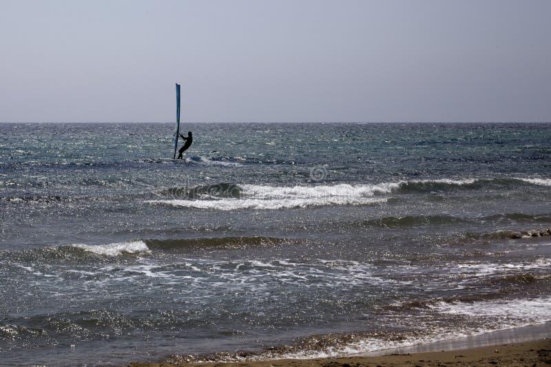 Surfer uit in de Oceaan die op Windsurfing-Raad in evenwicht brengen Blauwe Golf en Duidelijke Hemel Rider Directing Sail Mast te stock foto's