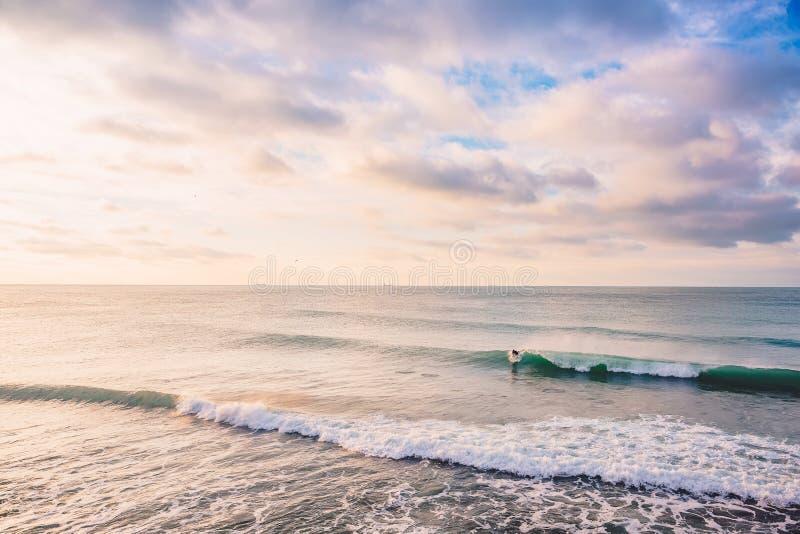 Surfer und Brechen der Fasswelle im Ozean Landschaft mit Sonnenaufgangfarben lizenzfreies stockbild