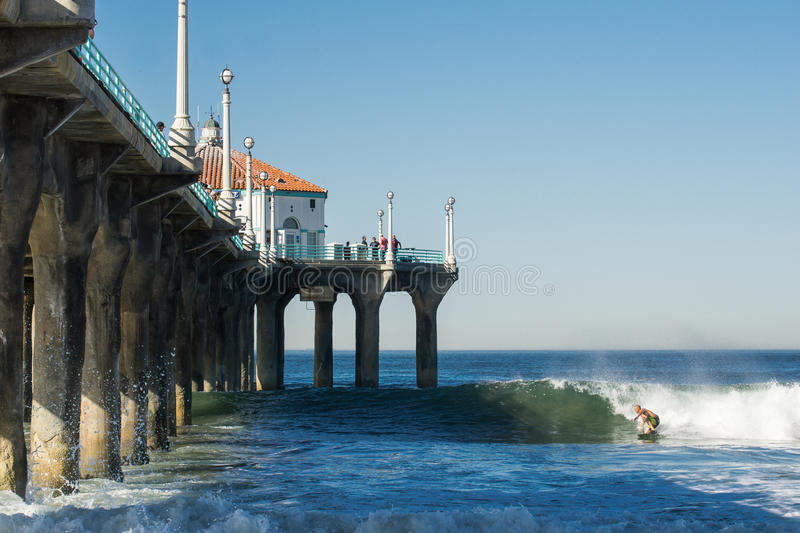 Surfer in wave heads into Manhattan Pier shadow in late afternoon surf California stock photos