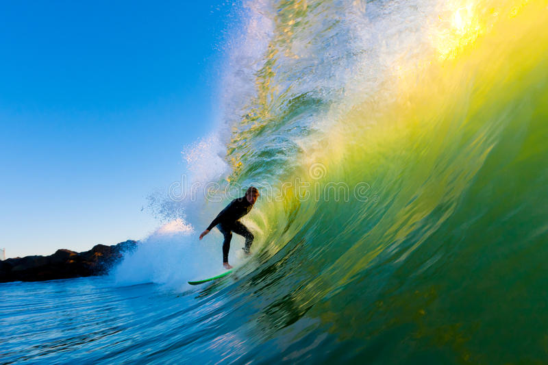 Surfer on Wave at Sunset. Surfer on Amazing Wave at Sunset, in the Barrel, Epic Tube royalty free stock photography