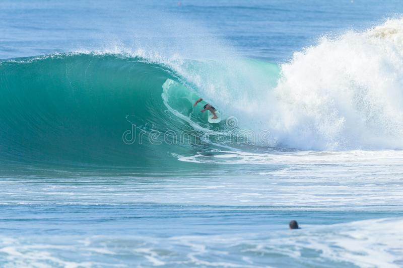 Surfer Wave Tube Surfing Action. Surfer surfing tube rides inside hollow ocean wave looking for the exit stock photos