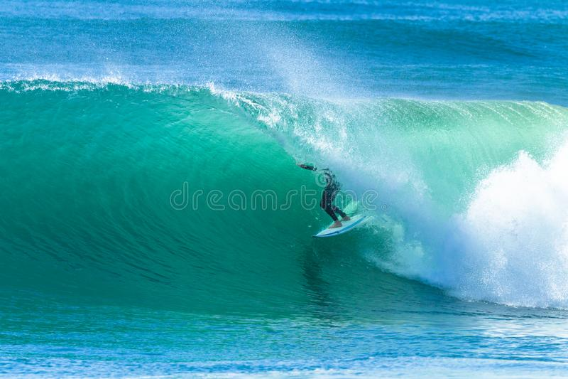 Surfer Wave Tube Surfing Action. Surfer surfing tube rides inside hollow ocean wave looking for the exit stock images