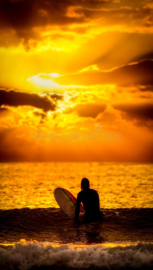 Surfer sunset wallpaper. Surfer on waves in ocean at sunset wallpaper, ratio to best fit mobile / cell screen background royalty free stock photos