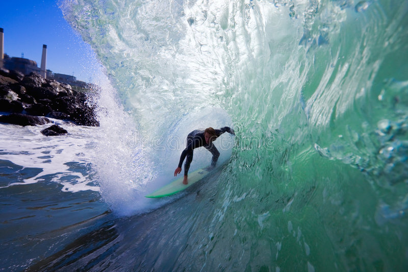 Surfer In The Wide Tube with Rocks. Surfer Gets an Epic Barrel On Big Wave with Beach in Background stock photo