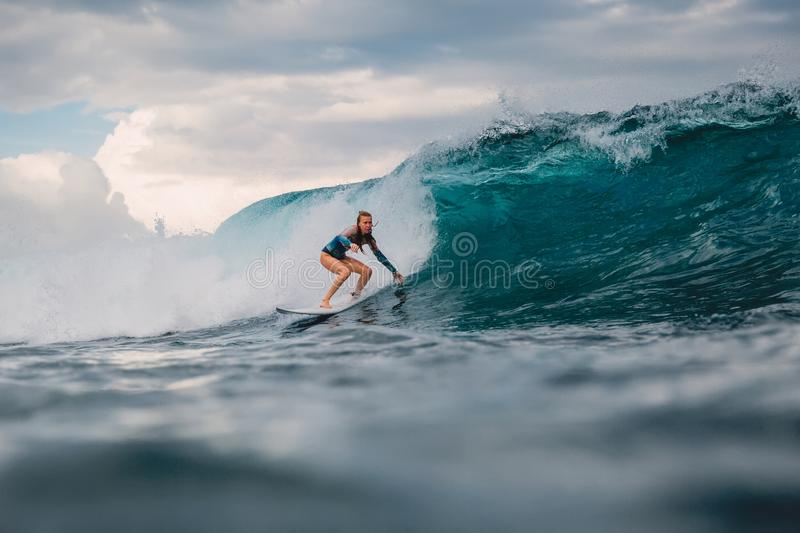 Surfer woman and big blue wave. Surf girl on surfboard. Surfer woman and big blue wave royalty free stock images