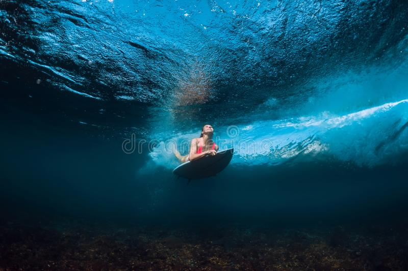 Surfer woman in bikini with surfboard dive underwater with under barrel ocean wave. Surfer woman in bikini with surfboard dive underwater with under barrel wave stock images