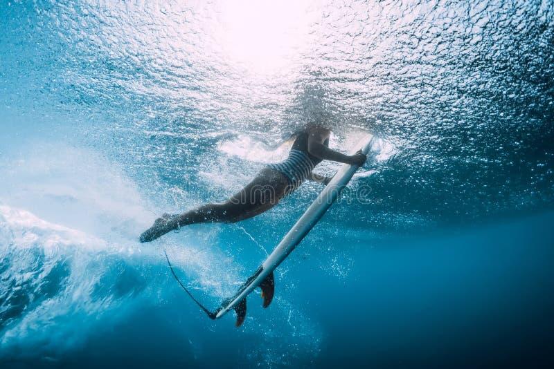 Surfer woman dive underwater. Surfgirl dive under wave stock photos