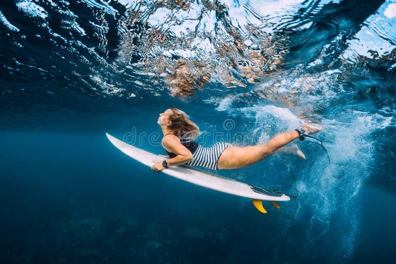 Surfer woman dive underwater. Surfgirl dive under wave royalty free stock photos