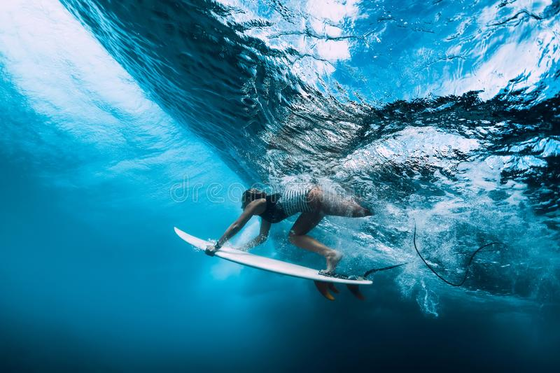 Surfer woman dive underwater. Surfgirl dive under wave royalty free stock image