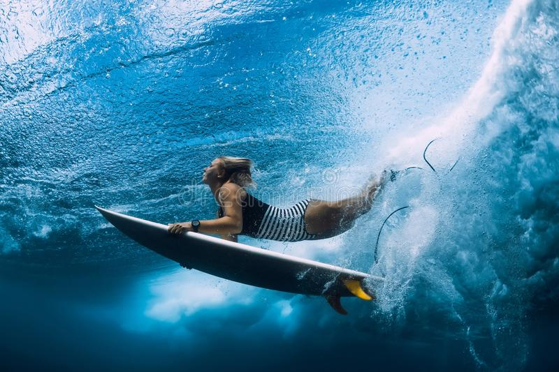 Surfer woman dive underwater. Surfgirl dive under wave royalty free stock images