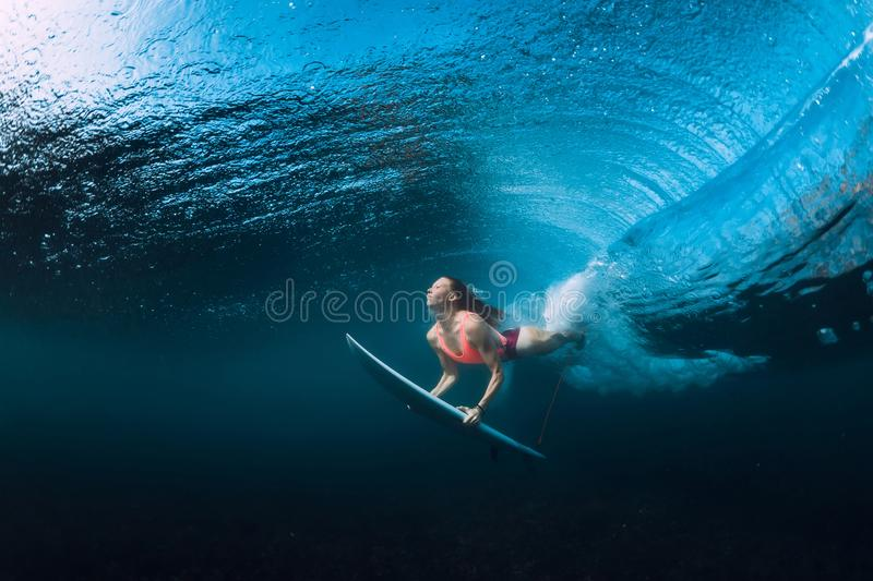 Surfer woman dive underwater with under wave. Surfer woman dive underwater with under barrel wave royalty free stock images