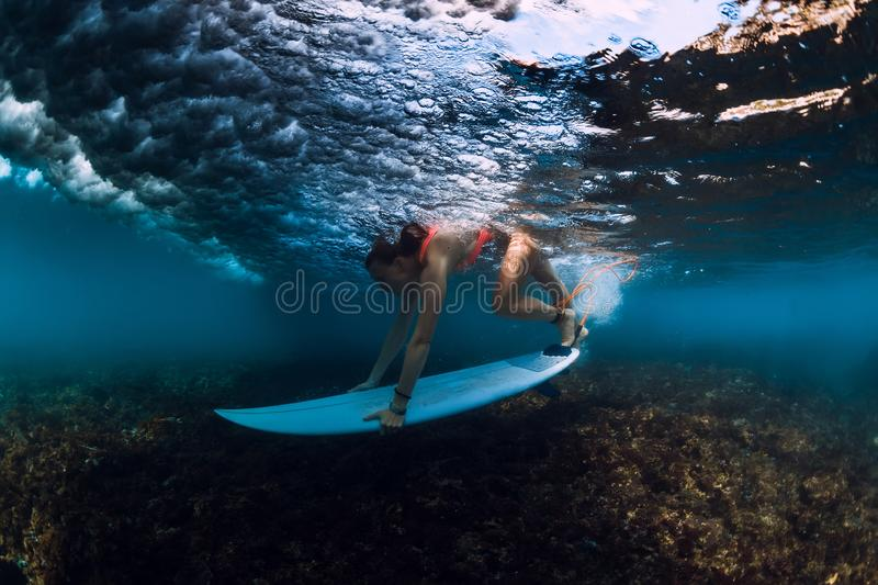 Surfer woman dive underwater with wave. Surfer woman dive underwater with under wave royalty free stock image