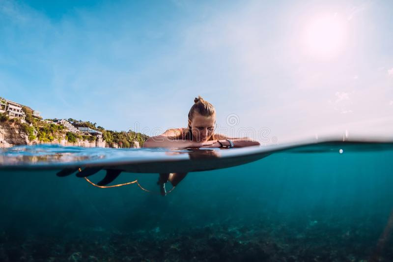 Surfer woman relax and floating with surfboard. Surfgirl in ocean. Surfer woman relax and floating with surfboard. Surfgirl in sea stock photo