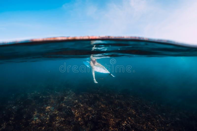 Surfer woman relax and sit at surfboard. Surf girl in blue ocean. Surfer woman relax and sit at surfboard. Surf girl in ocean stock images