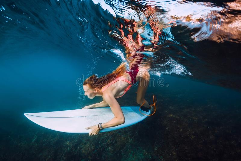 Surfer woman with surf board dive underwater with under big ocean wave. Surfer woman with surf board dive underwater with under big wave royalty free stock images