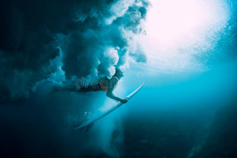 Surfer woman with surfboard dive underwater with under big wave. Surfer woman with surfboard dive underwater with under wave stock image