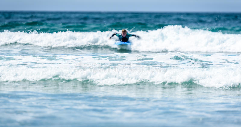Surfer woman with surfboard is paddling on the wave. stock photography