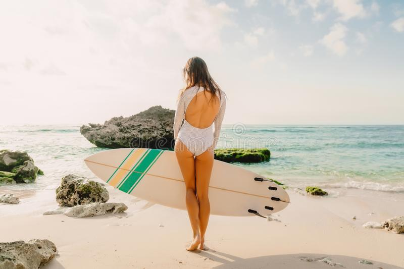 Surfer woman with surfboard. Surfing in ocean. Surfer woman with surfboard. Surfing in sea royalty free stock photo