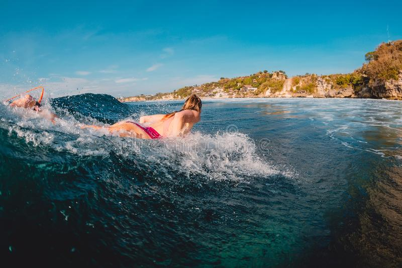 Surfer woman at surfboard on wave. Surf girl in ocean. Surfer woman at surfboard on wave. Surf girl in sea stock photography
