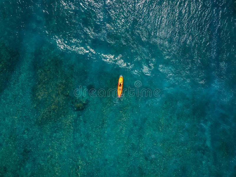 Surfer woman in tropical ocean waiting wave at yellow surfboard. Aerial view royalty free stock image