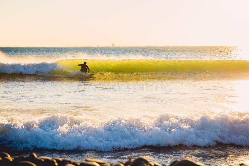Surferfahrt auf perfekten Meereswogen bei Sonnenuntergang Winter, der in Badeanzug surft lizenzfreie stockfotografie