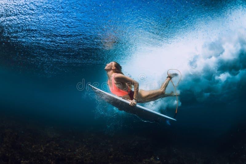 Surferfrau mit dem Surfbretttauchen Unterwasser lizenzfreie stockfotos