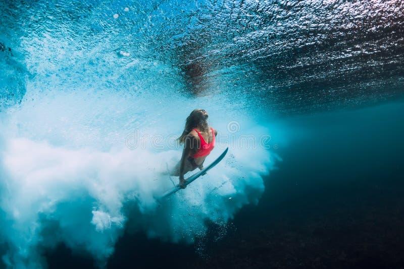 Surferfrau mit dem Surfbretttauchen Unterwasser mit Untermeereswogen lizenzfreie stockfotografie