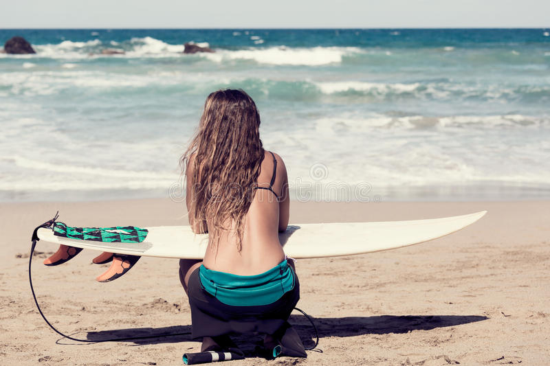 Surfergirl wating dla perfect fala z surfboard obrazy stock