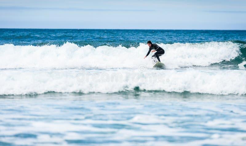 Surferkerl, der mit Surfbrett auf Wellen in Atlantik surft lizenzfreie stockfotos