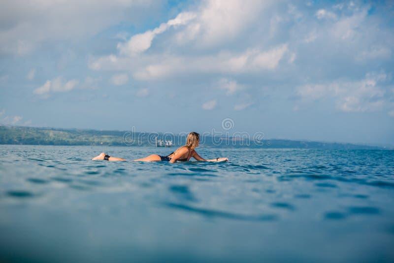 Surfermädchen auf dem Surfbrett Frau mit Surfbrett im Ozean lizenzfreie stockfotografie