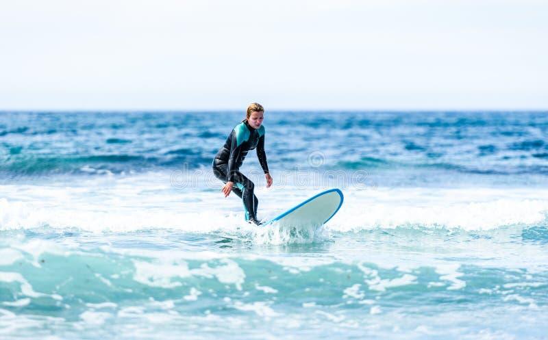 Surfermädchen, das mit Surfbrett auf Wellen in Atlantik surft stockfoto