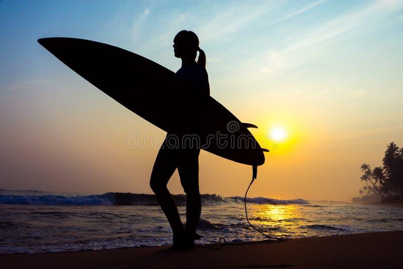 Surfermädchen, das Ozeanstrandsonnenuntergang betrachtend surft Schattenbild w lizenzfreies stockfoto