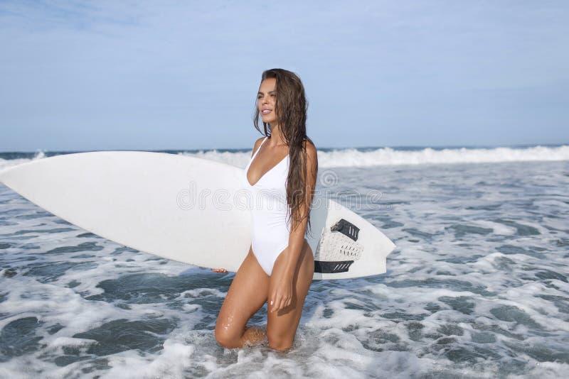 Surfermädchen in einem weißen Badeanzug geht zum blauen Ozean, mit einem weißen Surfbrett lizenzfreies stockfoto
