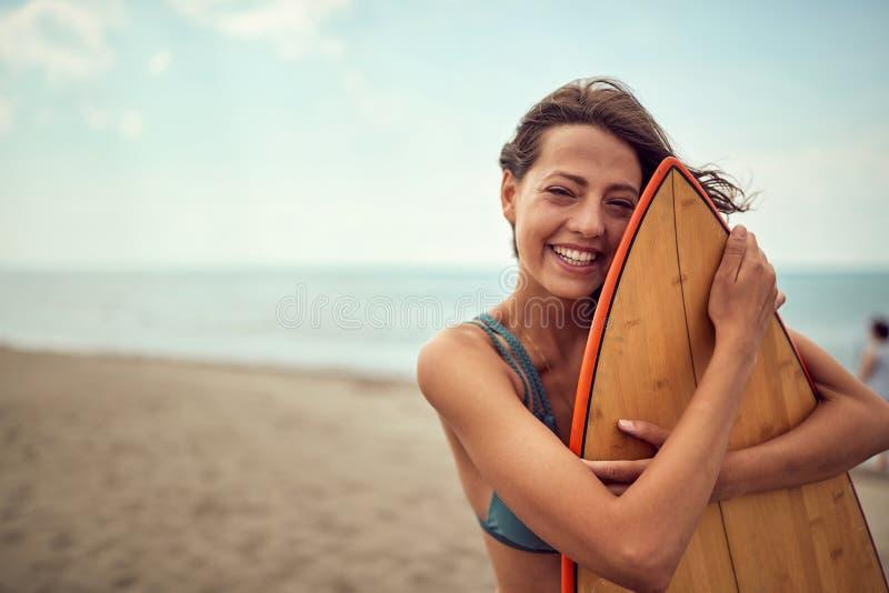 Surferm?dchen, das mit ihrem Surfbrett auf dem Strand aufwirft stockfoto