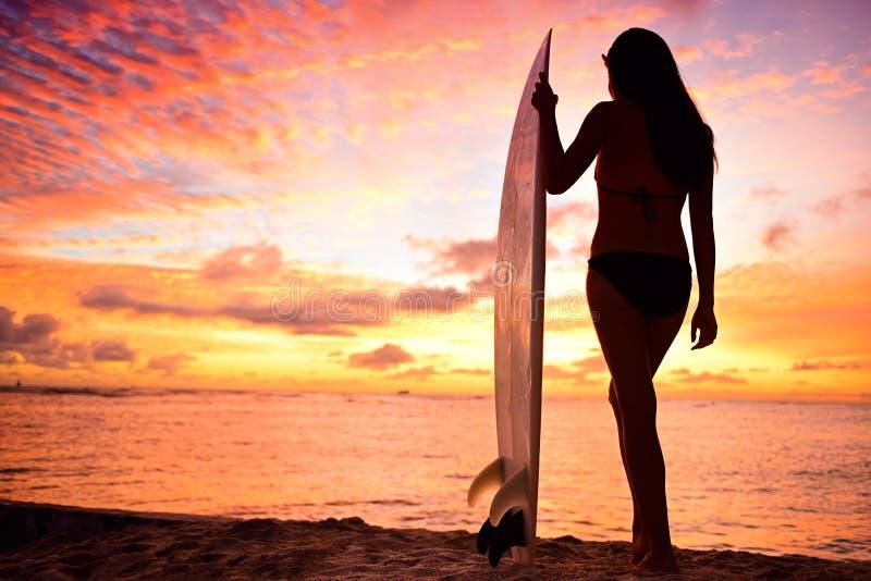Surfermeisje surfen die oceaanstrandzonsondergang bekijken royalty-vrije stock afbeeldingen
