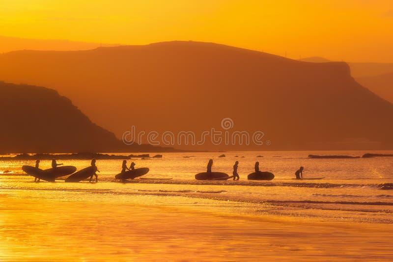 Surfermeisjes bij zonsondergang stock afbeelding