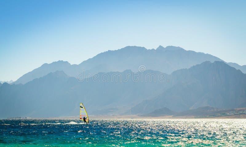 Surferritten in het overzees tegen de achtergrond van de hoge rotsachtige bergen in Egypte Dahab royalty-vrije stock fotografie