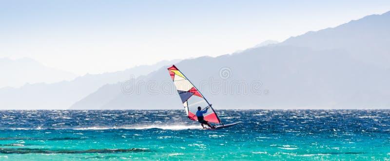 Surferritten in het Rode Overzees op de achtergrond van de rotsachtige kust in Egypte Dahab stock foto