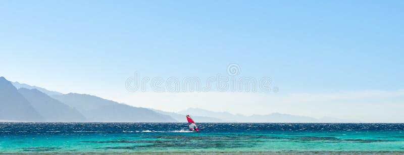 Surferritten in het Rode Overzees tegen de achtergrond van hoge rotsachtige bergen en een blauwe hemel met wolken in Egypte Dahab royalty-vrije stock foto's