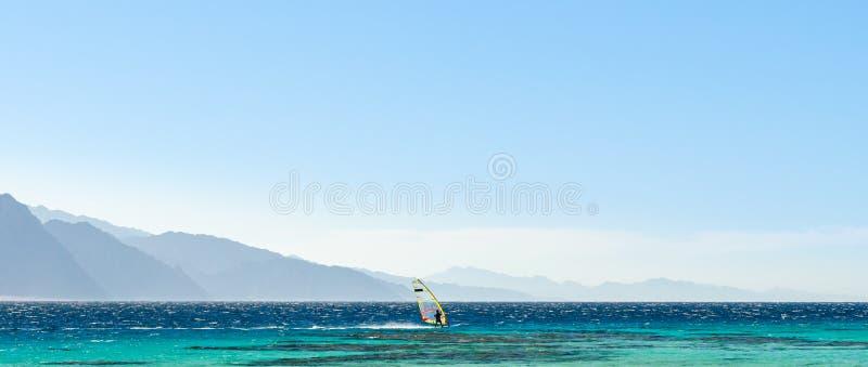 Surferritten in het Rode Overzees tegen de achtergrond van hoge rotsachtige bergen en een blauwe hemel met wolken in Egypte Dahab royalty-vrije stock afbeelding