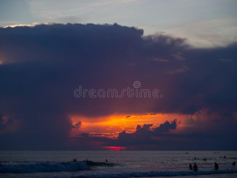 Surfers στο υπόβαθρο των όμορφων σύννεφων ηλιοβασιλέματος στοκ φωτογραφίες