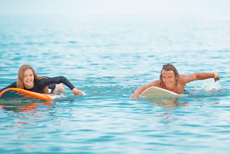 Surfers στο χαμογελώντας ζεύγος παραλιών των surfers που κολυμπούν και που έχουν τη διασκέδαση το καλοκαίρι Ακραία έννοια αθλητισ στοκ εικόνες