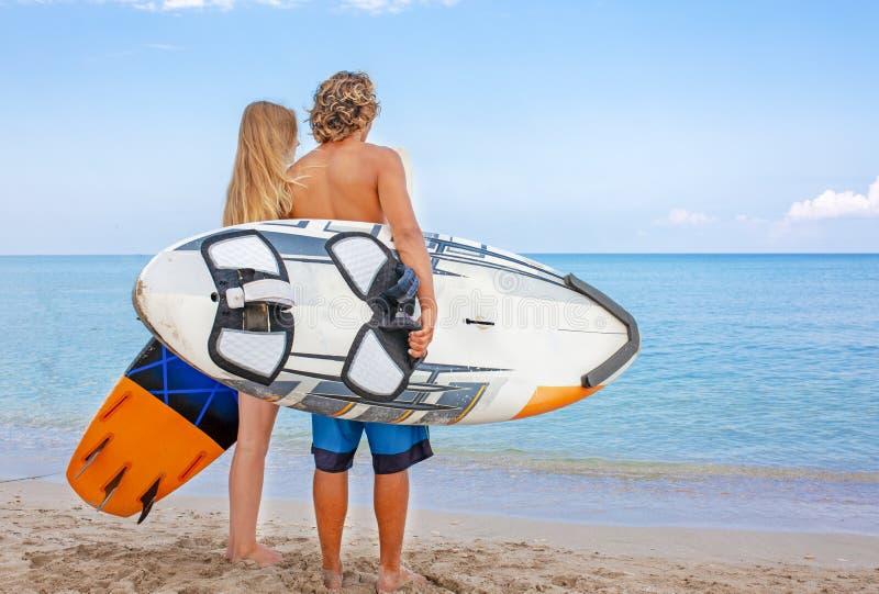 Surfers στο χαμογελώντας ζεύγος παραλιών των surfers που περπατούν στην παραλία και που έχουν τη διασκέδαση το καλοκαίρι Ακραίος  στοκ φωτογραφία