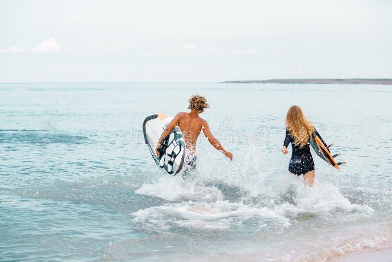 Surfers στο χαμογελώντας ζεύγος παραλιών των surfers που περπατούν στην παραλία και που έχουν τη διασκέδαση το καλοκαίρι Ακραίος  στοκ εικόνα