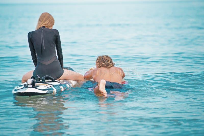 Surfers aux couples de sourire de plage des surfers nageant et ayant l'amusement en été Concept extrême de sport et de vacances image stock