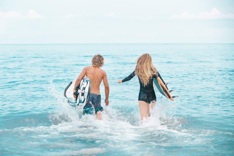 Surfers aux couples de sourire de plage des surfers nageant et ayant l'amusement en été Concept extrême de sport et de vacances photographie stock libre de droits