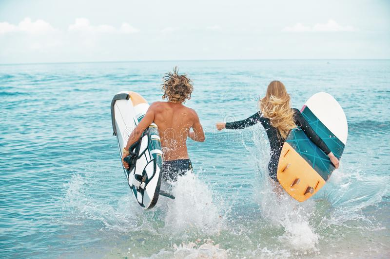 Surfers at the beach- Smiling couple of surfers run on the sea and having fun in summer. Extreme sport and vacation. Surfers at the beach- Smiling couple of stock photo
