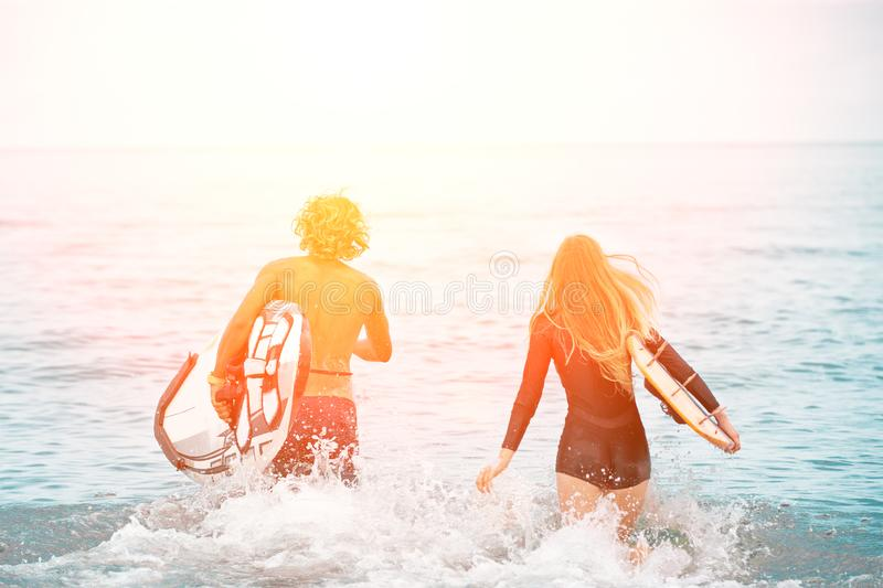 Surfers at the beach- Smiling couple of surfers run on the sea and having fun in summer. Extreme sport and vacation stock image