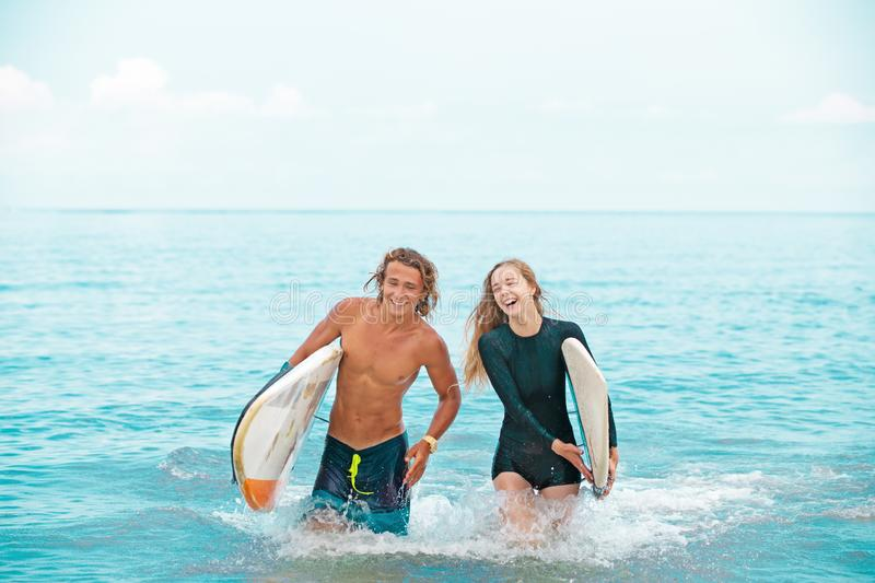 Surfers at the beach- Smiling couple of surfers walking on the beach and having fun in summer. Extreme sport and. Surfers at the beach- Smiling couple of surfers stock image