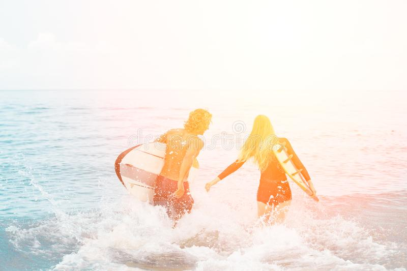 Surfers at the beach- Smiling couple of surfers walking on the beach and having fun in summer. Extreme sport and stock image